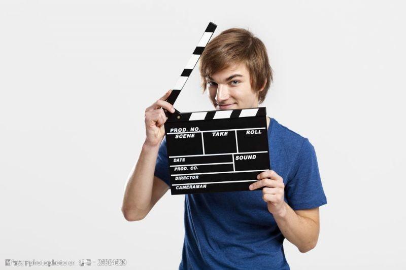 拍电影手拿场记板的青年导演图片