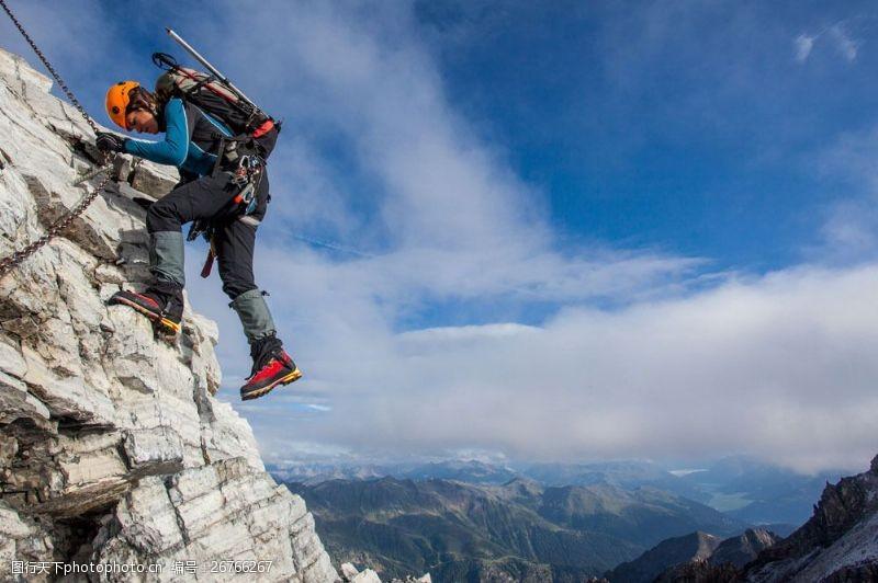 蓝天下登山的男人图片